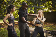 Two women with personal trainer explaining tree trunk shoulder lift in park - CUF16382