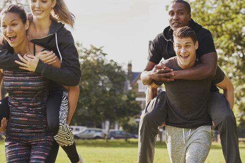 Men and women having fun training in park, having piggy back  race - CUF16388