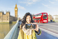 Young woman using smartphone to take selfie on Westminster bridge smiling, Thames river, London, UK - CUF16490