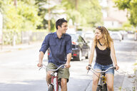 Young couple riding bicycle on street - CUF16568