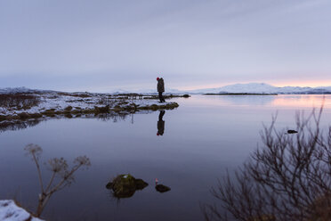 Man standing by lake on snow covered landscape, Thingvellir, Iceland - CUF16598