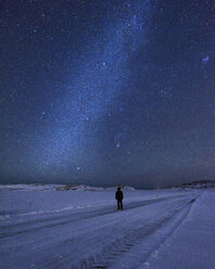 Man on snow covered landscape underneath starry night sky, Kleifarvatn, Iceland - CUF16601