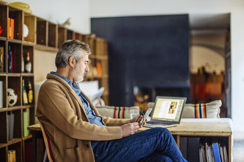 Mature man sitting in living room using smartphone and laptop - CUF16658