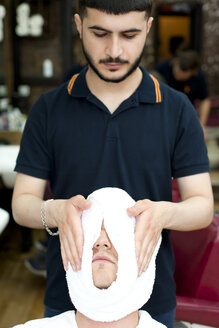 Barber wrapping young mans face in fresh towel, looking down - CUF16736