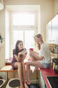 Two young woman sitting on kitchen counter chatting - CUF16829