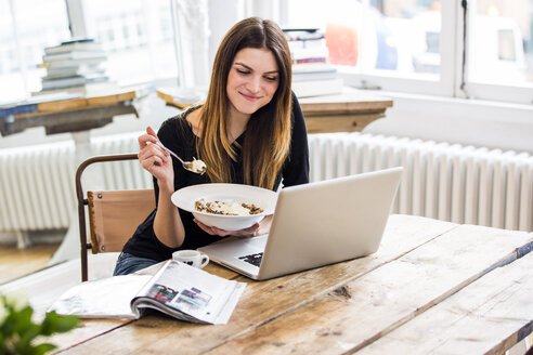 Young woman in city apartment eating muesli breakfast whilst reading  laptop - CUF16844