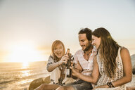 Three mid adult friends sitting on beach at sunset raising a toast, Cape Town, South Africa - CUF16943