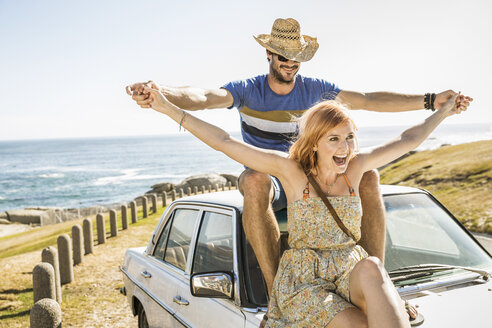 Mid adult couple with open arms on top of car on coast road, Cape Town, South Africa - CUF16961