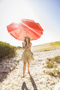 Mid adult woman carrying  beach umbrella at beach, Cape Town, South Africa - CUF16964