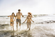 Three adult friends wearing bikini's and swimming shorts running in sea, Cape Town, South Africa - CUF16973