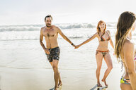 Mid adult couple wearing bikini and swimming shorts holding hands at beach, Cape Town, South Africa - CUF16976