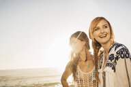 Two mid adult women on sunlit beach, Cape Town, South Africa - CUF16997