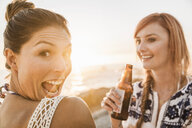 Portrait of two mid adult female friends pulling faces on beach at sunset, Cape Town, South Africa - CUF17018