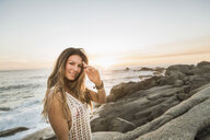 Portrait of mid adult woman on rocks at sunset, Cape Town, South Africa - CUF17021