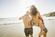 Rear view of couple carrying woman wearing bikini at beach, Cape Town, South Africa - CUF17030