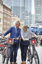 Mature dating couple laughing whilst pushing hire bicycles, London, UK - CUF17078