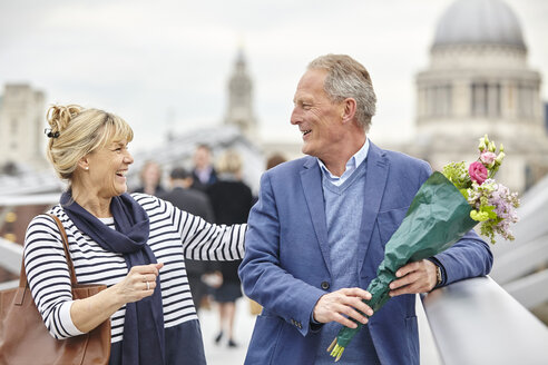 Romantic mature dating couple greeting on Millennium Bridge, London, UK - CUF17081