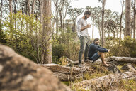 Two men drinking coffee on fallen tree in forest, Deer Park, Cape Town, South Africa - CUF17084
