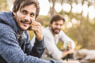 Two men sitting in forest drinking coffee, Deer Park, Cape Town, South Africa - CUF17087