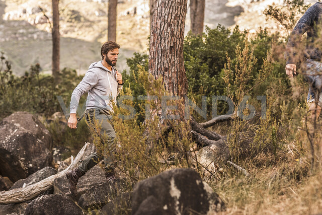 Male hiker hiking on forest rock formation, Deer Park, Cape Town, South Africa - CUF17096