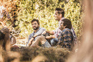Four male hikers taking a break in forest, Deer Park, Cape Town, South Africa - CUF17111