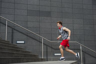 Young man exercising outdoors, running up steps - CUF17120