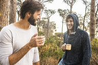 Two men drinking coffee and chatting in forest, Deer Park, Cape Town, South Africa - CUF17159