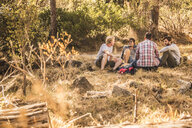 Four male hikers sitting chatting in forest, Deer Park, Cape Town, South Africa - CUF17162