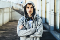 Man wearing hooded top and headphones, arms crossed looking at camera - CUF17291