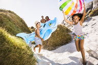 Family with two children running down sand dune carrying shark inflatable and beachball, Cape Town, South Africa - CUF17330