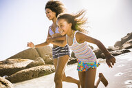 Girl and mother running on beach, Cape Town, South Africa - CUF17339