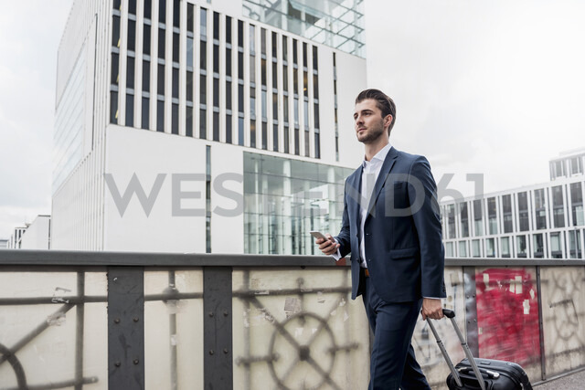 Young businessman with cell phone and rolling suitcase in the city on the go - DIGF04526 - Daniel Ingold/Westend61