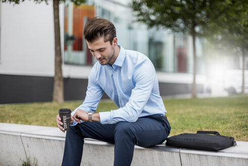 Young businessman sitting outdoors with takeaway coffee checking the time - DIGF04535