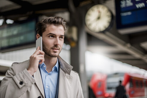 Businessman at the station on cell phone - DIGF04544
