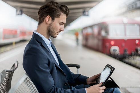 Businessman at the station using tablet - DIGF04550