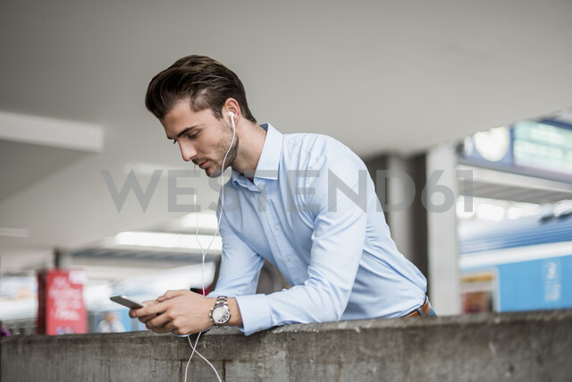 Businessman with cell phone and earbuds at the station - DIGF04553