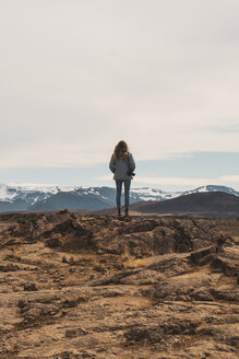 Iceland, female photographer standing on rocks, rear view - KKAF01084