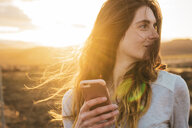 Iceland, woman using smartphone at sunset - KKAF01093