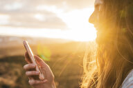 Iceland, woman using smartphone at sunset - KKAF01096