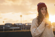 Iceland, young woman with coffee to go at sunset - KKAF01114