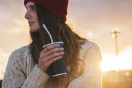 Iceland, young woman with coffee to go at sunset - KKAF01117