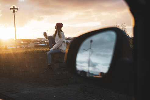 Iceland, young woman with coffee to go at sunset, wing mirror - KKAF01120