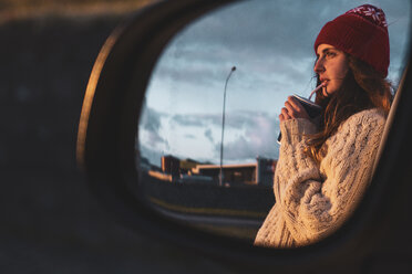 Iceland, young woman with coffee to go at sunset, mirrored in wing mirror - KKAF01123