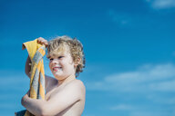 Portrait of happy boy with beach towel outdoors - MJF02290