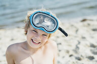 Portrait of happy boy wearing diving goggles on the beach - MJF02293
