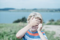 Smiling boy outdoors covering his eyes - MJF02296