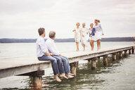 Group of friends on pier, female friends walking towards male friends sitting on edge of pier - CUF17387