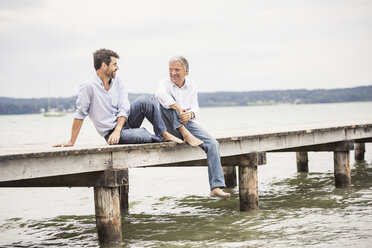 Mature male friends relaxing on pier - CUF17393