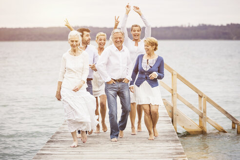 Group of friends walking together on pier - CUF17396