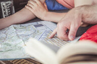 Close up man and teenage son hands pointing at map whilst lying in vehicle - CUF17414